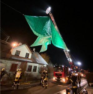 Die Feuerwehr hebt mit der Drehleiter das Notdach an, um es anschließend über dem Dachfirst abzulassen